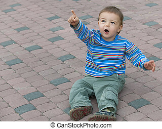 Sitting on the pavement toddler is showing a plain in the sky