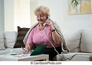Sitting on the sofa and talking on landline phone
