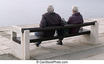 Sitting quietly - Elderly couple sitting on a bench by the...