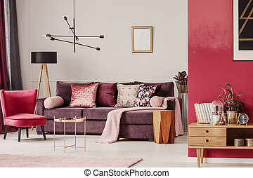 Sitting room interior with purple couch, red armchair and...