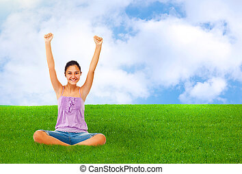 Sitting teenage girl on grass while rejoices with arms up. -...