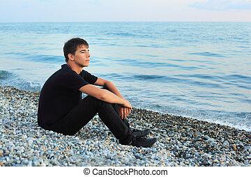 sitting teenager boy on stone seacoast, Looking afar