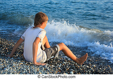sitting teenager boy on stone seacoast, wets feet in water, ...