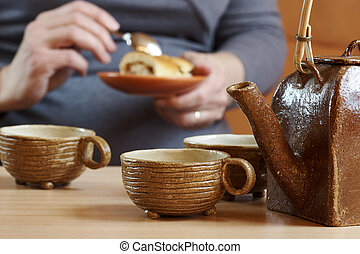 Sitting woman eating her dessert with a spoon at a cup of tea and a teapot