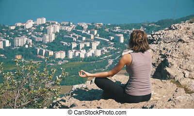 Sitting woman in lotus position practicing yoga moves. Cliff...