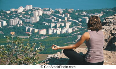 Sitting woman in lotus position practicing yoga moves. Cliff top with the cross.