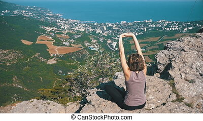 Sitting woman in lotus position practicing yoga moves or meditates and Raises her arms up in mountains.
