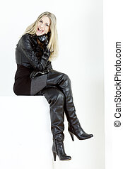 sitting woman wearing fashionable black boots