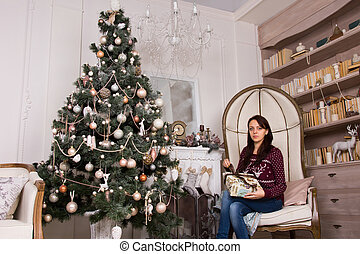 Sitting woman with presents near Christmas tree