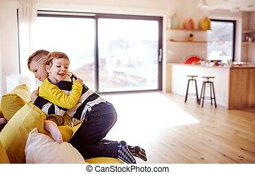 sitzen, sofa, zwei kinder, innen, hugging., daheim, glücklich