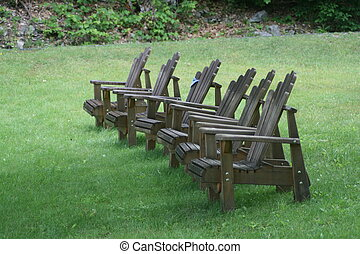 Six Adirondack chairs in a line on the lawn