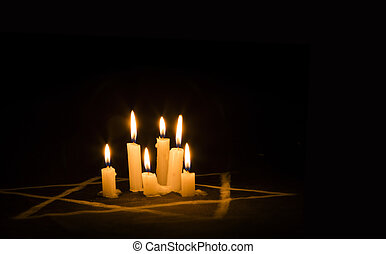 Six burning candles and the Star of David against a black...