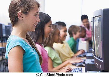 Six children at computer terminals with teacher in...