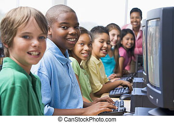 Six children at computer terminals with teacher in background (selective focus/high key)