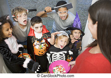 Six children in costumes trick or treating at woman\\\'s house