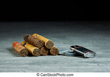 Six Cuban cigars on a stone table with lighter and cutter