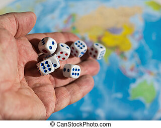 Six dice roll with a man's hands on world map. World order. d map and money