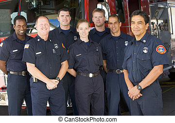 Six firefighters standing in front of fire engine with captain (depth of field)