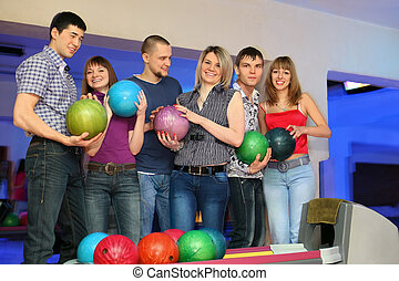 Six friends stand near stand ruling balls and everybody holds ball for bowling