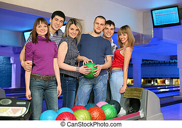 Six friends stand near stand ruling balls and going to play in bowling