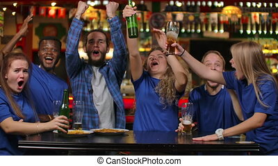 Six friends watch the match and rejoice at a caring goal, an...