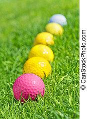 six golf balls on the green grass