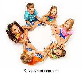 Six kids sit in a lotus pose