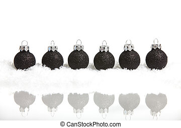 Six little black christmas tree balls in the snow mirrored, on white background