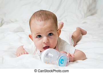 Six month baby girl with big brown eyes pulls hands to a bottle of water with open mouth. She wants to drink. Lying on a white bed. Infant in pink white clothes.