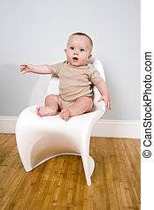 Six month old baby sitting on a chair