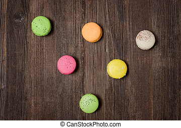 Six multicolored macarons on a brown wooden table. Top view