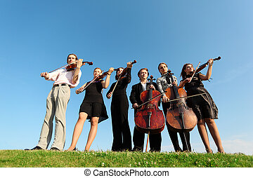 Six musicians play violins against sky