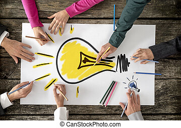 Six people, men and women, drawing bright yellow light bulb on a large sheet of paper or placard
