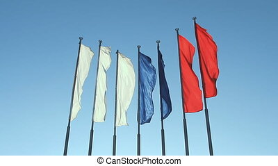 Six red, blue and white flags flutt