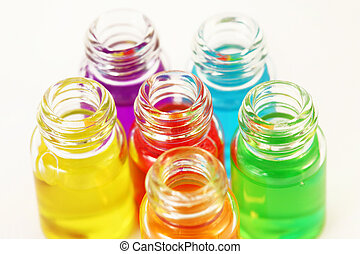 Six small opened glassy bottles of different colored aromatic oils
