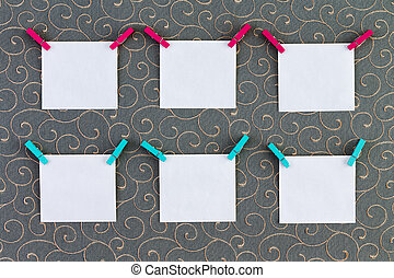 Six square tags with clothespins attached