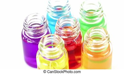 Six transparent open bottles spins with color oil on them