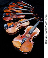 six violins with black background