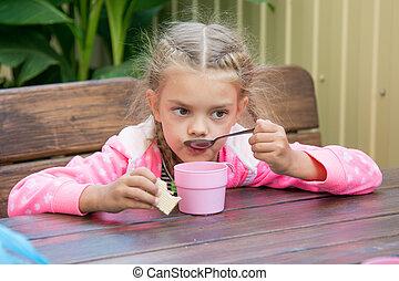 Six-year girl drinks tea from a spoon breakfast on the veranda