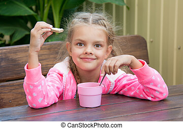 Six-year girl has breakfast on the veranda