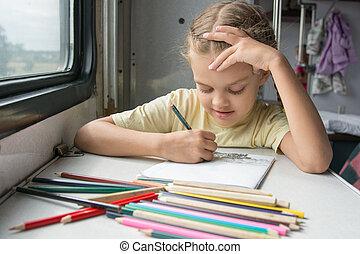 Six-year girl joyfully draws pencils in second-class train carriage