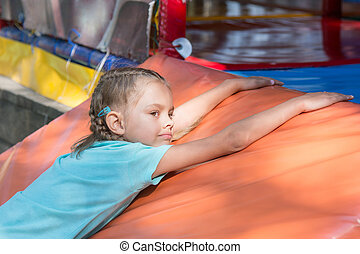 Six-year girl lies on a soft mat in front of the childrens room