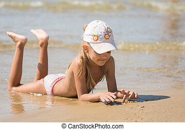 Six-year girl lies on the sand of the sea, and drawing with your fingers in the sand