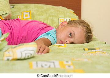 Six-year girl lying across the bed, trying to sleep