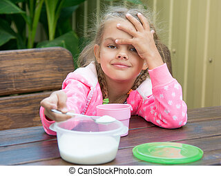 Six-year girl pours sugar in tea spoon a small breakfast on the veranda