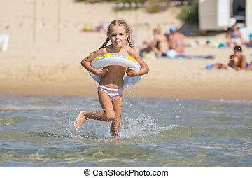 Six-year girl runs with a swimming circle swim in the sea