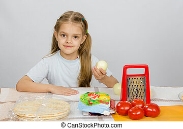 Six-year girl sitting at the kitchen table in front of her are vegetables, base and other ingredients for pizza