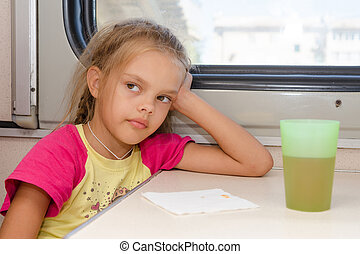 Six-year girl thoughtfully and tired sitting on the train at the table in the second-class compartment