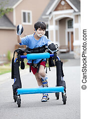 Six year old disabled boy walking in walker down the street