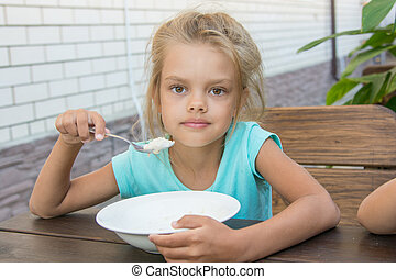 Six year old girl at a wooden table in the yard eating porridge